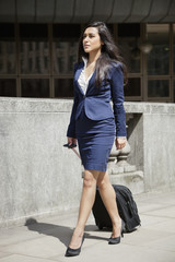 Indian businesswoman in formal clothing walking with wheeled bag