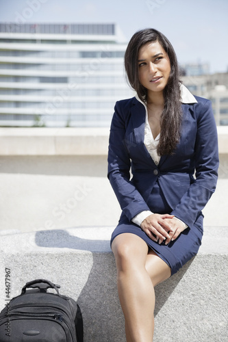 Young Indian businesswoman with bag sitting outdoors