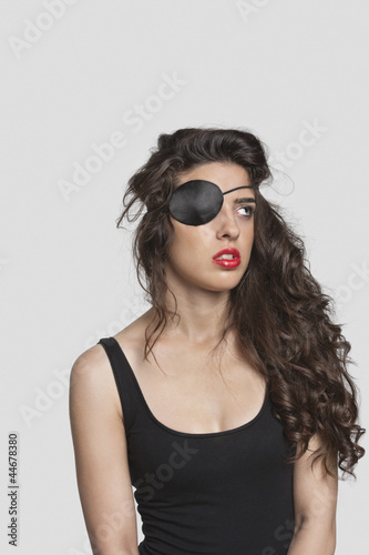 Thoughtful young woman wearing eye patch over gray background