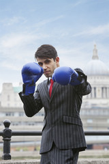 Indian businessman wearing blue boxing gloves with St. Paul's Cathedral in the background