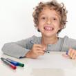 Kleiner Junge schreibt mit bunten Stiften