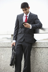 Young Indian businessman texting through cell phone while holding laptop bag at parapet