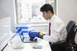 Young Indian businessman wearing boxing gloves while using laptop at office desk