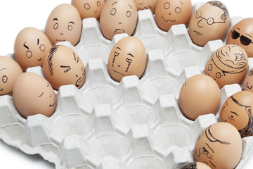 Variety of facial expressions painted on brown eggs arranged in carton