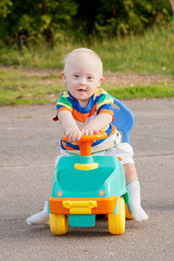 smiling baby boy with Down syndrome who driving toy car