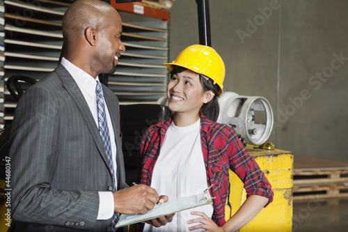 Female industrial worker looking at male inspector as he writes on clipboard