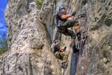 Two men in camouflage done rappelling on rock