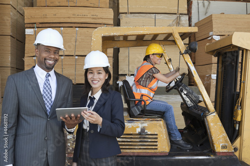 Happy multiethnic engineers holding tablet PC with female worker driving forklift truck in background