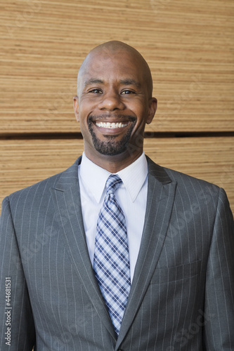 Portrait of African American businessman smiling with stacked wooden planks in background