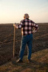 male farmer with spade  back