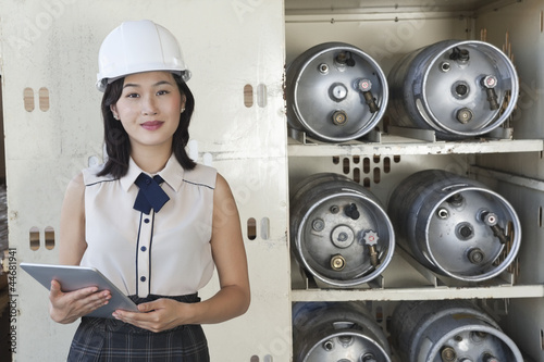 Portrait of female industrial worker holding tablet PC with cylinders on shelf in background