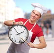 portrait of young cook man pointing a clock at street
