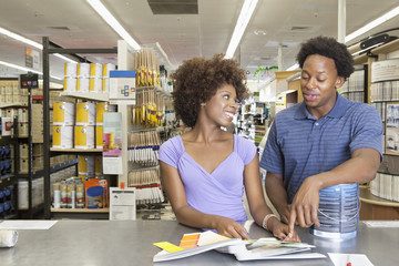 Young African American couple buying painting tools at super market