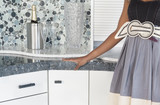 Midsection of woman with champagne set on kitchen counter