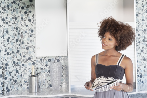 Young African American woman looking at designed wall as she holds design swatches