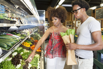 Young African American couple buying green vegetables at supermarket