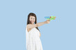 Happy young woman aiming with a toy gun over blue background