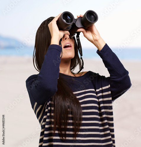 portrait of young woman looking through a binoculars against a b