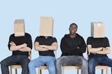 Man with friends faces covered with cardboard boxes as they sit on chairs over blue background