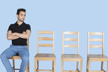 Portrait of a young man sitting beside empty wooden chairs over blue background