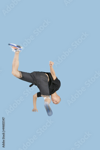 Teenage boy break dancing over blue background