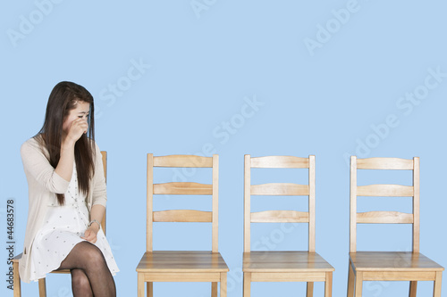 Young woman crying besides empty wooden chairs over blue background