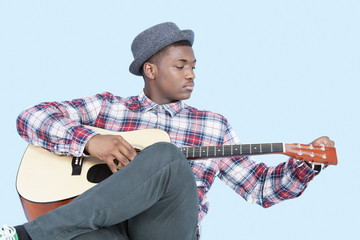 Young African American man tuning guitar over light blue background