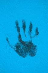 Graffitti palm print on blue painted wall