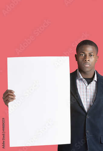 Portrait of a young man holding blank cardboard over pink background