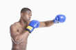 Young African American boxer boxing over gray background