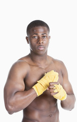 Portrait of a shirtless African American kickboxer over gray background
