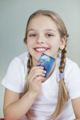 Portrait of a girl holding credit card over gray background
