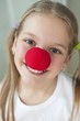 Close-up portrait of a happy girl with red clown nose