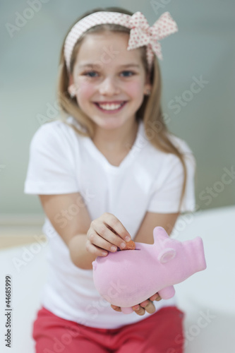 Portrait of a happy girl putting coin in piggy bank