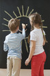 Back view of siblings drawing sun on blackboard