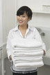 Portrait of beautiful housemaid holding white towels