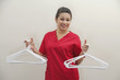 Portrait of female housekeeper holding white plastic hangers against gray background