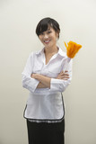 Portrait of female housekeeper holding feather duster against gray background