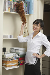 Portrait of female housekeeper dusting shelf