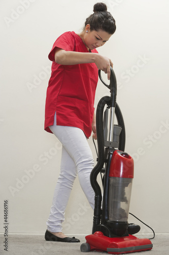 Full length of female housekeeper using vacuum cleaner