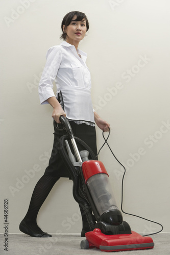 Full length of young female housekeeper vacuuming