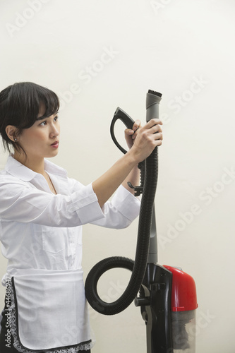 Female housekeeper holding vacuum cleaner pipe against gray background