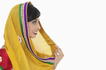 Side view of Indian female holding dupatta over white background