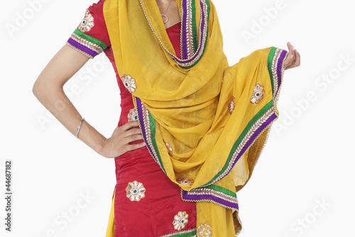 Midsection of woman in traditional wear standing with hand on hip over white background