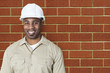 Portrait of happy young construction worker with hardhat over brick wall