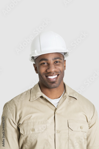 Portrait of happy young African male construction worker over gray background