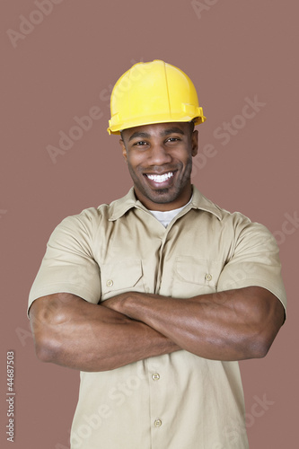 Portrait of cheerful young African construction worker over brown background