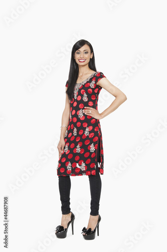 Full length portrait of Indian female in traditional wear standing with hand on hip over gray background