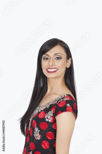 Portrait of Indian woman smiling against gray background