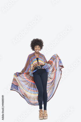 Full length portrait of an attractive African American in traditional wear standing over gray background